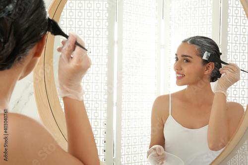 Fototapeta Young woman applying dye on hairs near mirror indoors obraz
