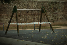 Cordoned Off A-frame Swing In A Kids Playground Tied With Tape To Prevent Usage With Old Brick Wall Background