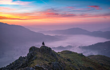 Fiery Dawn Over The Misty Valley Of Grasmere In The Beautiful Lake District, With Lone Hiker In The Distance