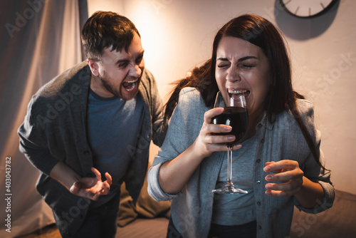 Canvastavla drunk man screaming at alcohol-addicted wife holding wine glass with closed eyes