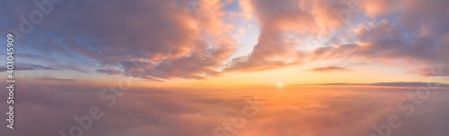 Obraz Sunrise panorama in lilac and pale pink shades with cirrus clouds. Sky background. View from the plane during the flight on vacation - fototapety do salonu