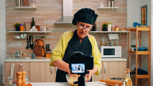 Billede på lærred Woman communicating with subscribers through video camera while kneading dough