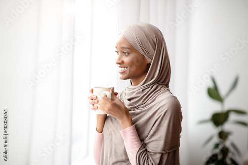 Obraz Attractive black woman in hijab with cup of hot coffee looking out window at home, enjoying her hot drink - fototapety do salonu