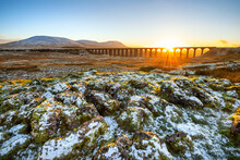 Golden Light On A Cold Winter Evening At Ribblehead Viaduct In North Yorkshire With Snow Covered Rocks In Foreground.