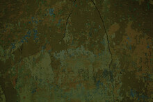 Grungy Cement Wall With Cracks And Old Dingy Green Paint Remnants In A Full Frame View