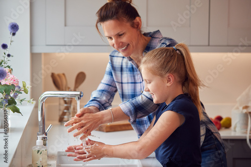 Obraz Mother And Daughter Washing Hands With Soap At Home To Stop Spread Of Infection In Health Pandemic - fototapety do salonu