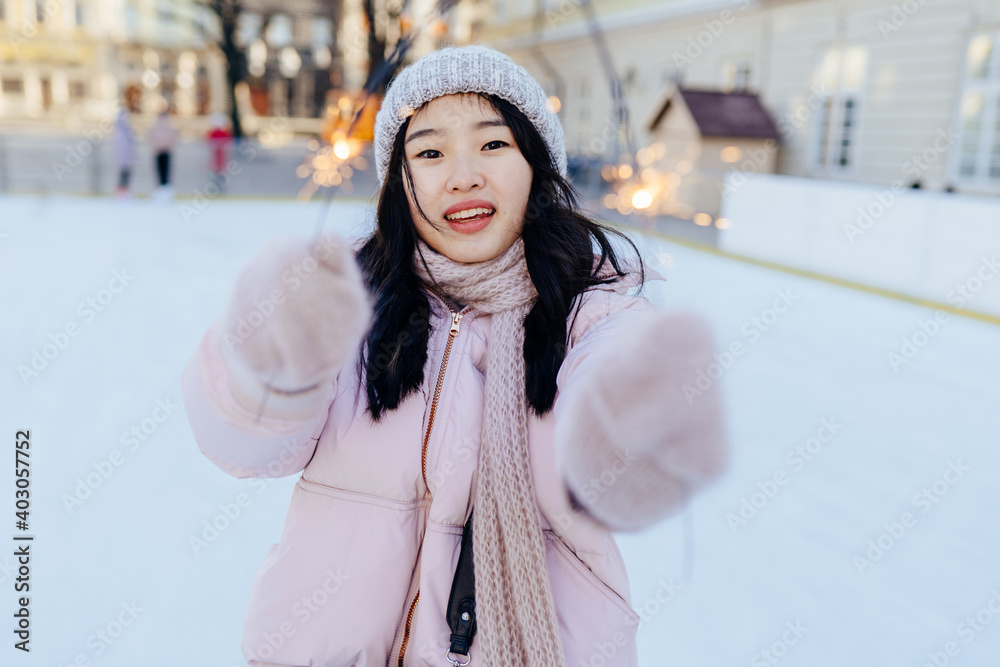 Fototapeta Lovely korean female with bengal lights with inspired smile spending vacations in european square to skate on rink. Asian woman in warm pink jacket, knitted hat, scarf, gloves in winter cold weather.
