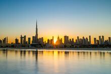 Sunrise In Dubai With Clean Blue Sky View From Boat Or Sea. The Sun Rises Over UAE Skyscrapers At Morning. Dubai Beach, Coast, Shore