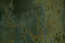 Background Texture Of Cracked Concrete Wall With Remnants Of Old Green Paint In A Full Frame View