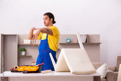 Canvas Print Young male carpenter stealing jewelry at home