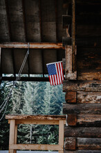 American Flag Hanging Outside An Old Homestead Cabin In The Woods