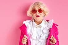 Amazed Elderly Female In Stylish Clothes Posing At Camera Isolated On Pink Background, Surprised Emotional Lady In Sunglasses