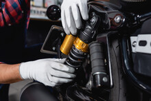 Cropped View Of Mechanic Checking Shock Absorber Of Motorcycle In Workshop