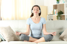 Woman With Headphones Meditating Doing Yoga On A Couch