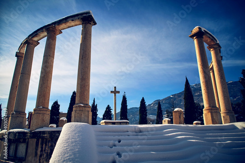 Fotografie, Obraz Snowy italian cemetery with colonnade and cross in the center