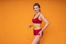Beautiful, Smiling, Blonde Woman In Underwear Measuring Fit Body After Diet With A Centimeter Tape.