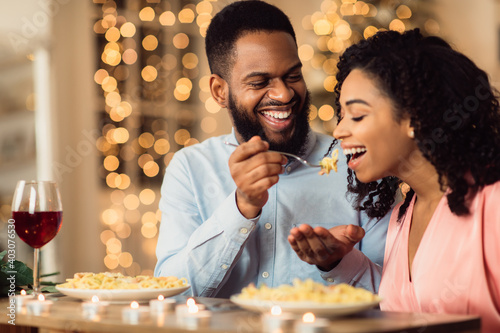 Smiling black man feeding his woman on a date