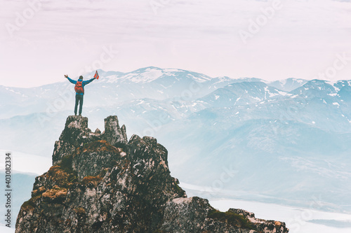 Obraz Man climbing on mountain top adventure travel outdoor extreme active lifestyle vacation tour hiking in Norway success raised hands Husfjellet peak - fototapety do salonu