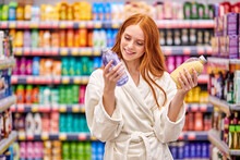 Female Is Comparing Bath Salts In The Household Goods Department, Choose The Best Product. Woman With Red Hair In Bathrobe Enjoy Shopping