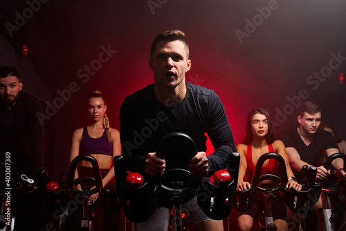 group of people in the gym, exercising their legs doing cardio training, having spinning class at gym in dark neon lighted smoky space