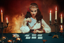 Fantasy Beautiful Magnificent Girl In Image Of A Gypsy Sits At Table In Dark Gothic Room. Red Costume, Vintage Clothing, Art Black Make Up. Fortune Teller Woman Reading Future On Magical Tarot Cards.