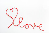 Valentine's day concept. Red heart and word love made from woolen rope on white background with copy space.