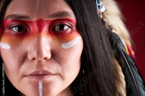 Fotografia close-up portrait in native american style, beautiful woman in Indian hat and drawings on face, trendy color photo