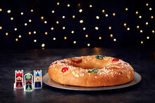 Christmas Scene..Three Kings Cake With Candied Fruit And Almonds On A Gray Plate. Three Figures Of The Three Wise Men To One Side. In The Background Christmas Lights.