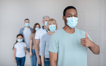 Black Guy In Face Mask Waiting In Queue For Coronavirus Vaccination At Clinic, Showing Thumb Up Gesture, Copy Space