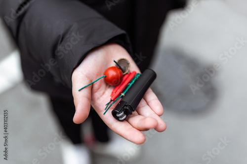 Fototapeta Boy lighting up several firecrackers in his hand using lighter