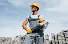 Posing For A Camera With Circular Saw. Male Worker In Yellow Colored Uniform Have Job With Pavement