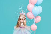 Unicorn Girl. Joyful Child Girl In Elegant Tulle Dress And Unicorn Headband Celebrates Birthday  Party And Blowing Multicolored Confetti On Cyan Background