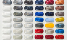 Paint Samples When Choosing A Car Color. Background Palette For Choosing The Colors Of The New Car. Dealership Acrylic Small Car Figures Many Different Colors.