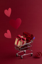 St. Valentine's Festive Sale Concept With Gift Box Rose, And Red Paper Hearts In The Shopping Cart Against A Red Background.