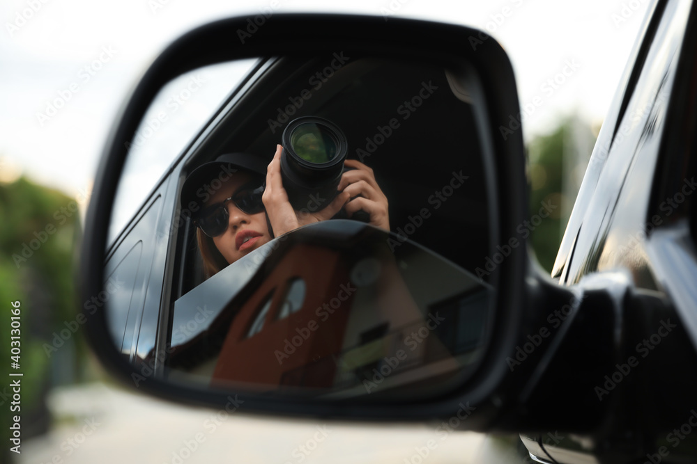 Fototapeta Private detective with camera spying from auto, view through car side mirror