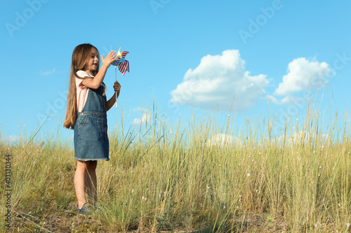 Obraz na plátne Cute little girl with pinwheel outdoors, space for text