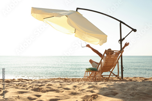 Stampa su Tela Man relaxing on deck chair at sandy beach. Summer vacation