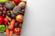 Wooden Crate Full Of Harvested Vegetables And Fruits On Light Table, Top View. Space For Text