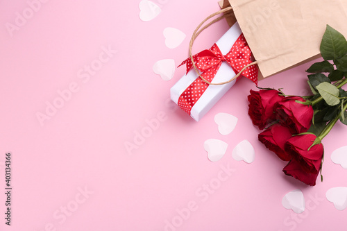 Beautiful gift box, roses and hearts on pink background, flat lay with space for text. Valentine's day celebration