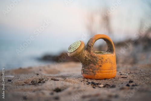 Fotografia an orange plastic watering can found along the empty beach