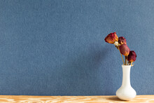 Vase Of Dry Red Rose On Wooden Table. Blue Background. Flower Arrangement