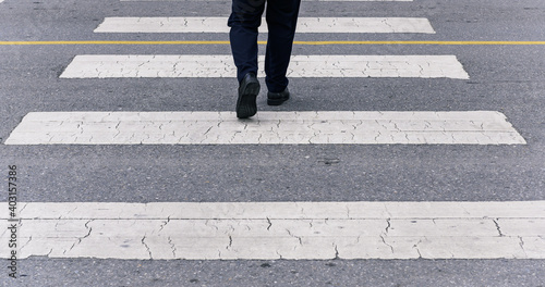 Canvas Back view of businessman crossing the street on crosswalk