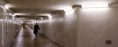 Silhouette of businessman walking in dark underground passage 暗い地下道を歩くビジネスマンのシルエ Fototapet