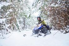 Man On Snowmobile In Winter Mountain. Snowmobile Driving. Man Driving Snowmobile In Snowy Forest