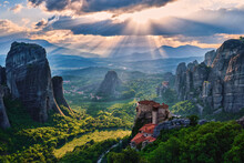 Sunset View Of Nunnery Of Moni Agias Varvaras Roussanou And Rocks Of Meteora, Greece And Valley. Cloudy Sky, Sun Rays Fall Upon. UNESCO World Heritage