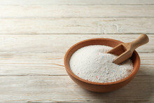 Bowl With Washing Powder And Scoop On Wooden Background