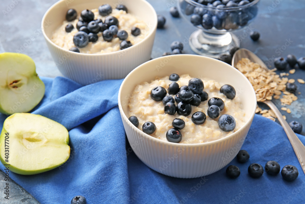 Fototapeta Bowls with tasty oatmeal and blueberry on color table