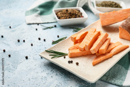 Tray with raw sweet potato on color background