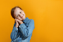 Cute Little Girl In A Denim Shirt On A Yellow Background. The Child Folded Her Palms And Lowered Her Head On Them.