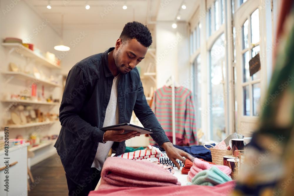 Fototapeta Male Small Business Owner Checks Stock In Shop Using Digital Tablet